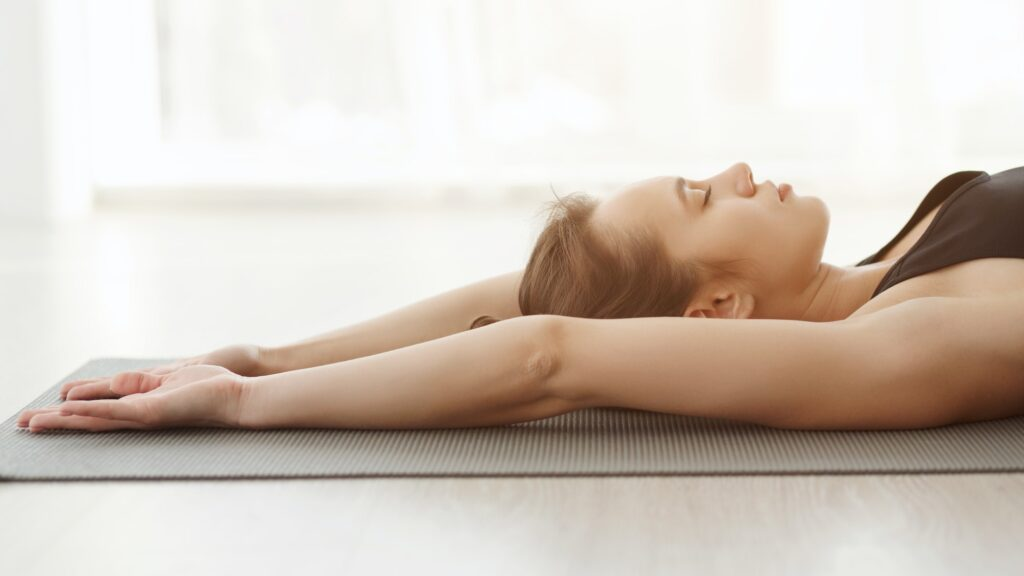 Relaxed yoga girl laying on mat, doing breathing exercise